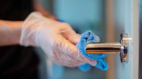 Cleaning door handle with disinfectant