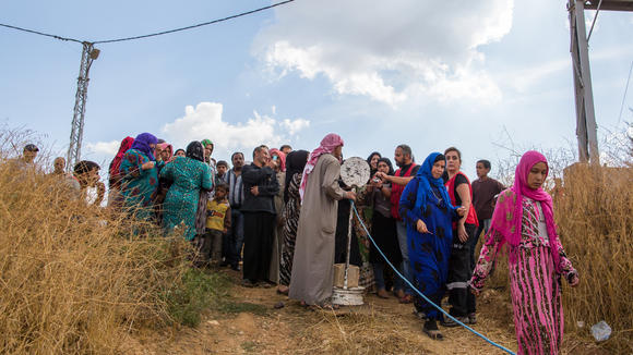 Refugees waiting to receive aid packages from humanitarian aid organisations in the Beqaa region Lebanon.